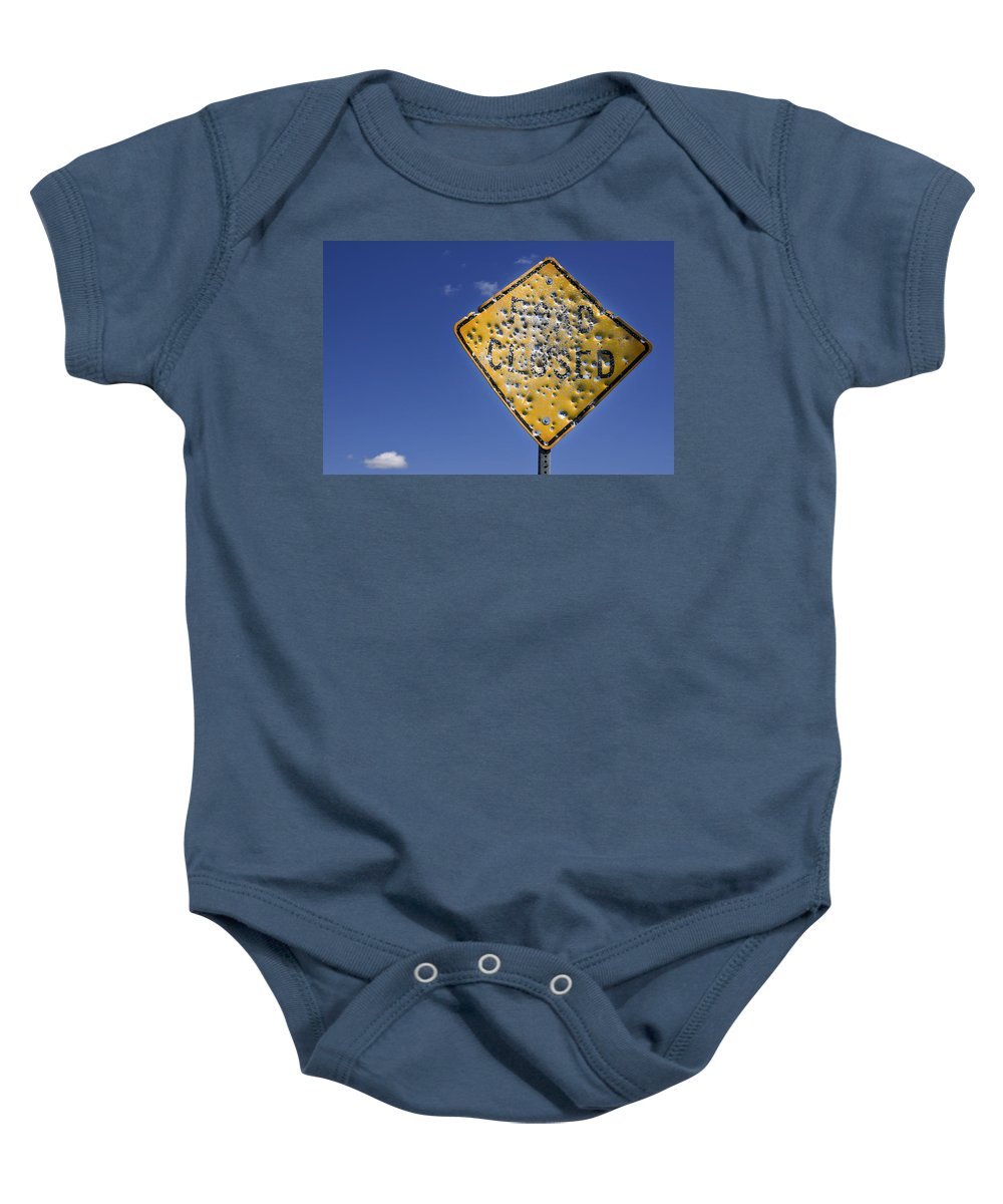 Close Up Baby Onesie featuring the photograph Vandalized Road Sign Many Bullet Holes by Donald Erickson