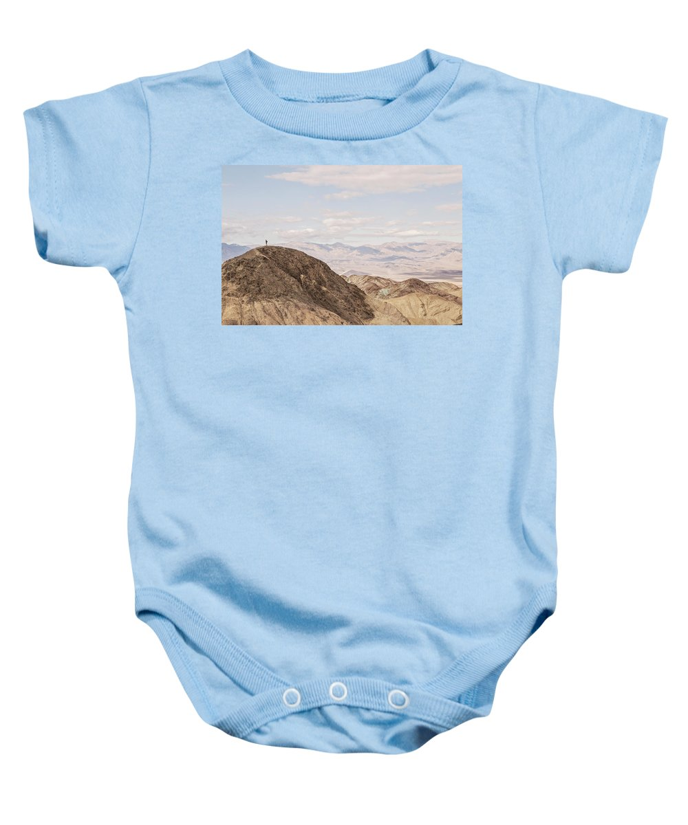 Arid Baby Onesie featuring the photograph A Hiker Stands On A Peak by Chris Bennett