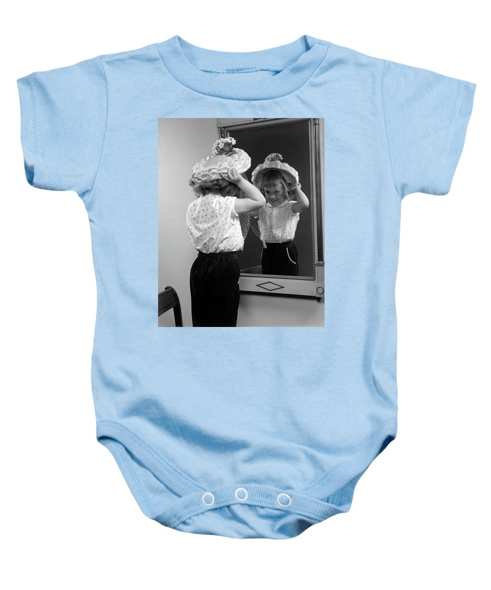 Photography Baby Onesie featuring the photograph 1950s Little Girl Trying On Hat Looking by Vintage Images