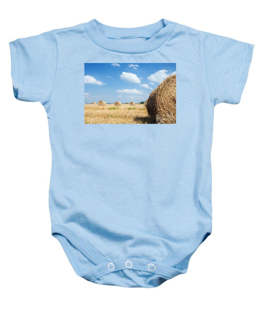 Harvest Baby Onesie featuring the photograph Haystacks In The Field by Michal Bednarek