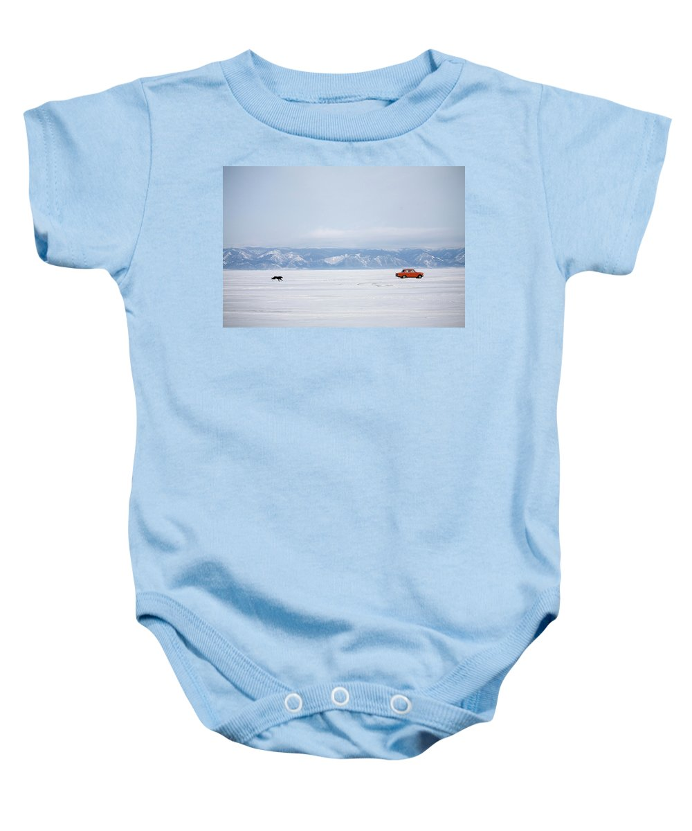 Animal Baby Onesie featuring the photograph A Dog Chases After A Car On The Frozen by Olivier Renck