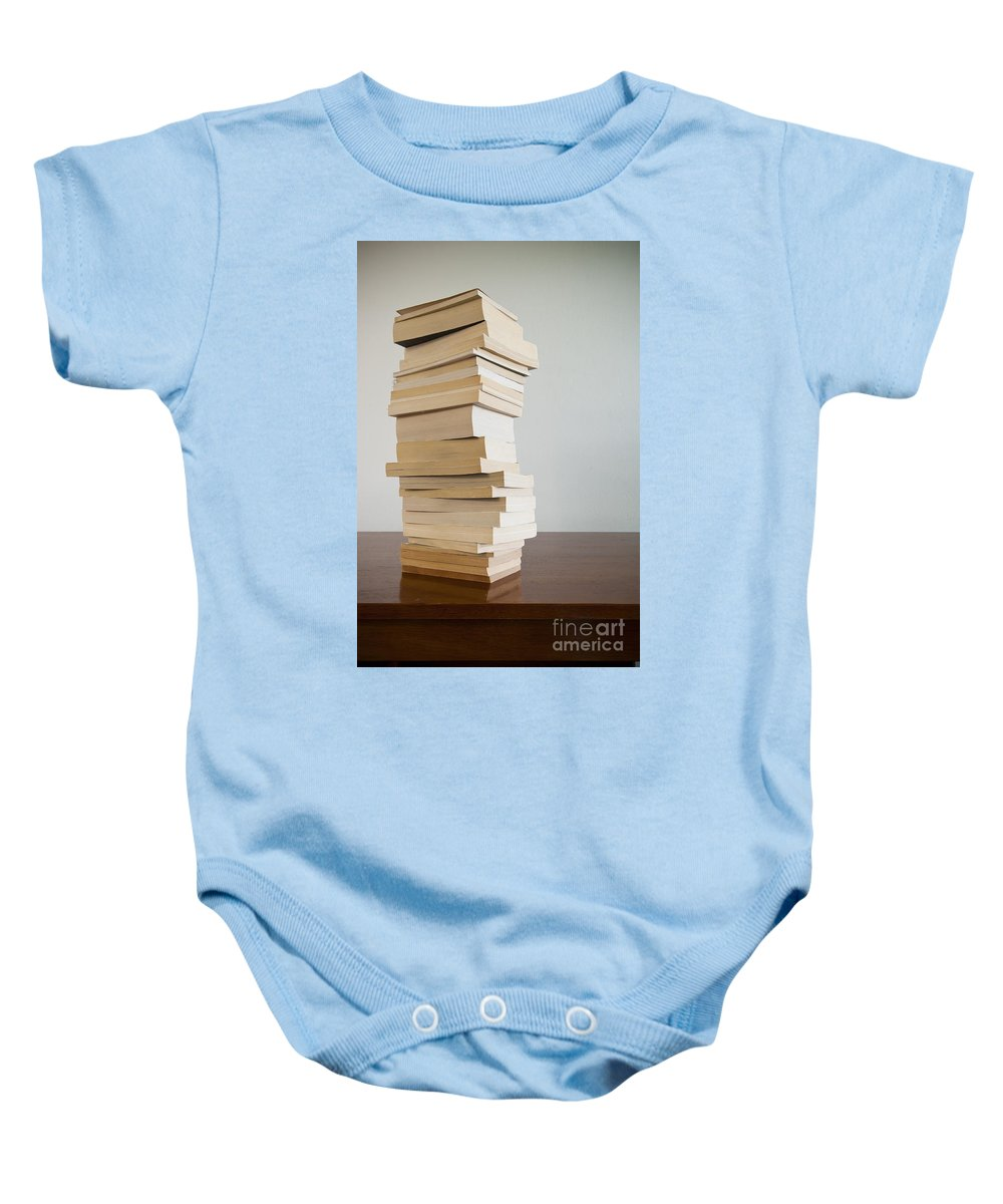 Book Baby Onesie featuring the photograph Book Stack On Table by Tim Hester