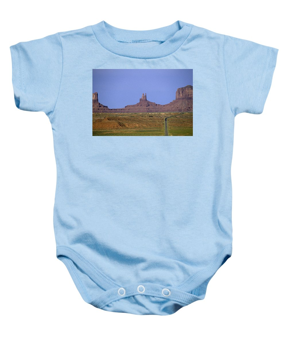 Adventure Baby Onesie featuring the photograph Highway 163 Leading Into Monument Valley With Rock Formations In by Jim Corwin