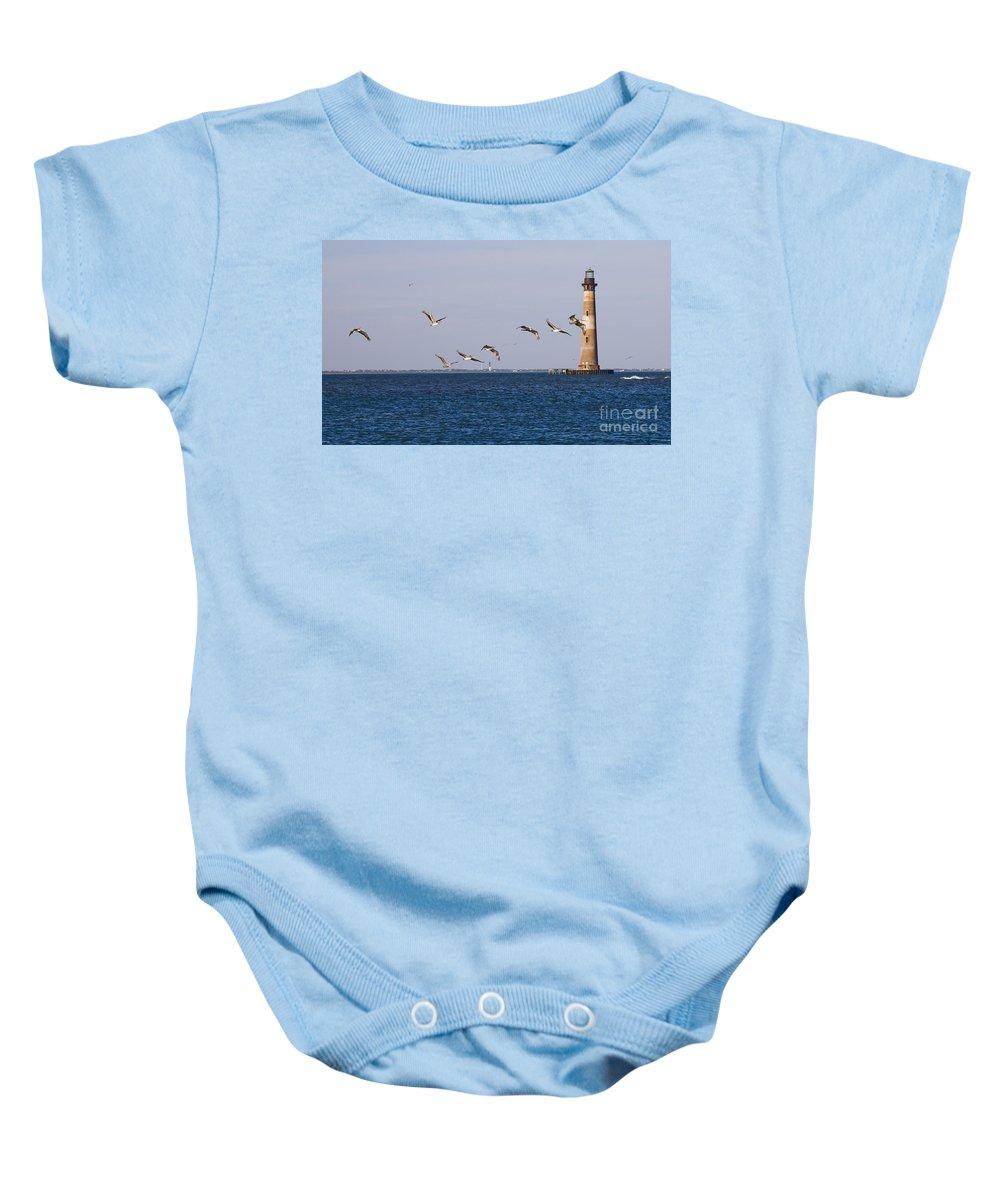 Morris Island Light Baby Onesie featuring the photograph Pelicans And Morris Island Light 1 by Tim Mulina