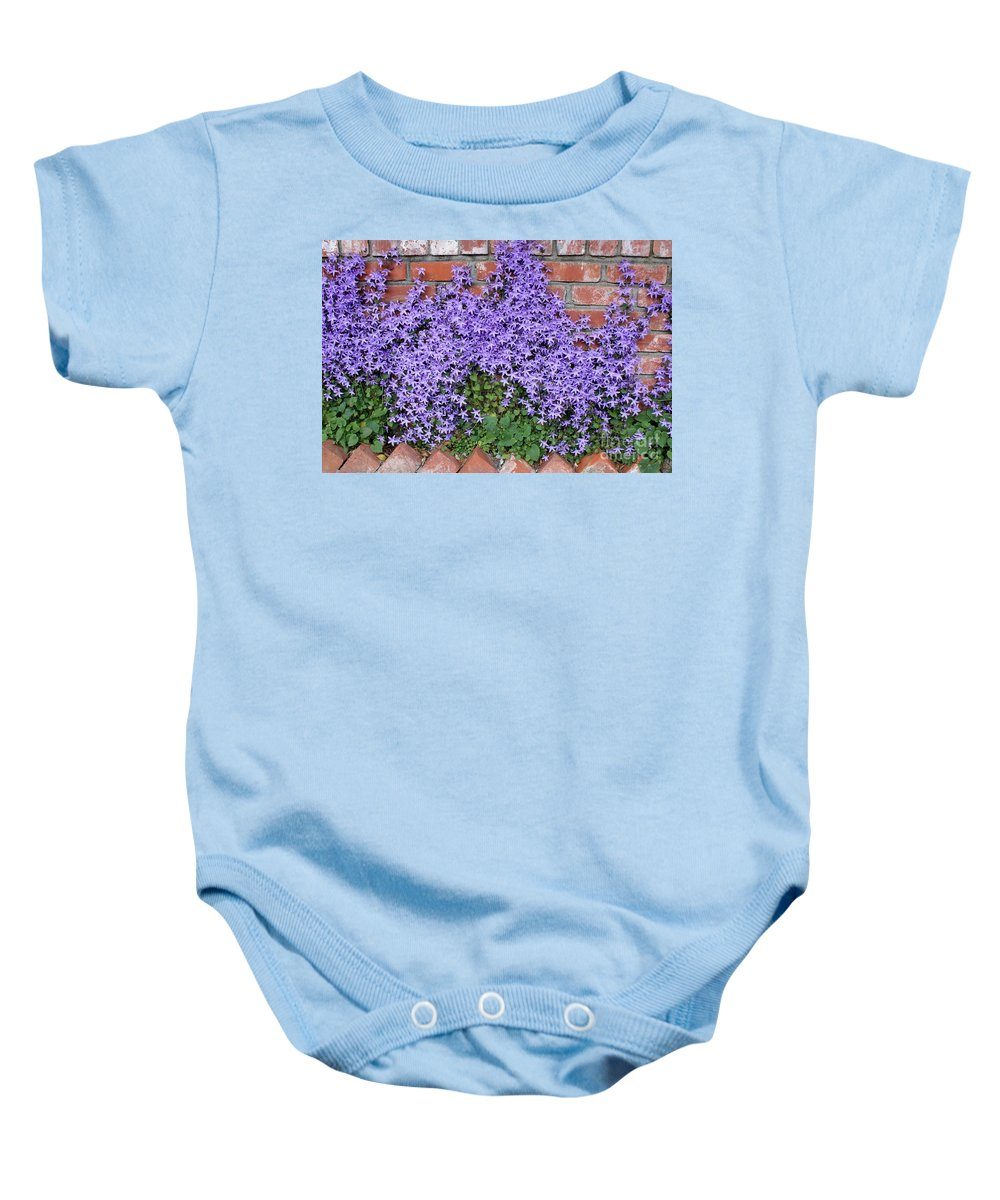 Blue Flowers Baby Onesie featuring the photograph Brick Wall With Blue Flowers by Carol Groenen