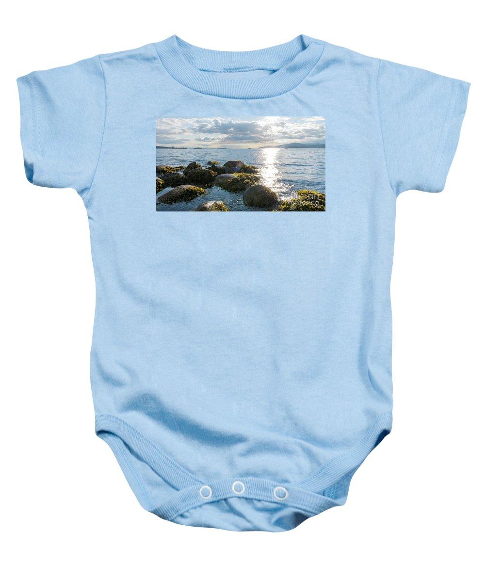 Ocean Baby Onesie featuring the photograph Ocean Flickering Under Sunset by Josephine Cleopahrt