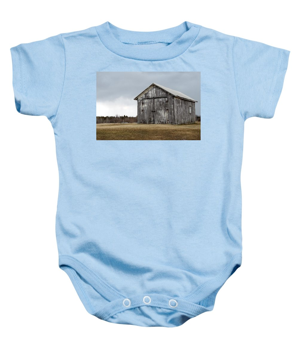 Sky Baby Onesie featuring the photograph Rustic Barn With Dark Clouds by Nadine Mot Mitchell