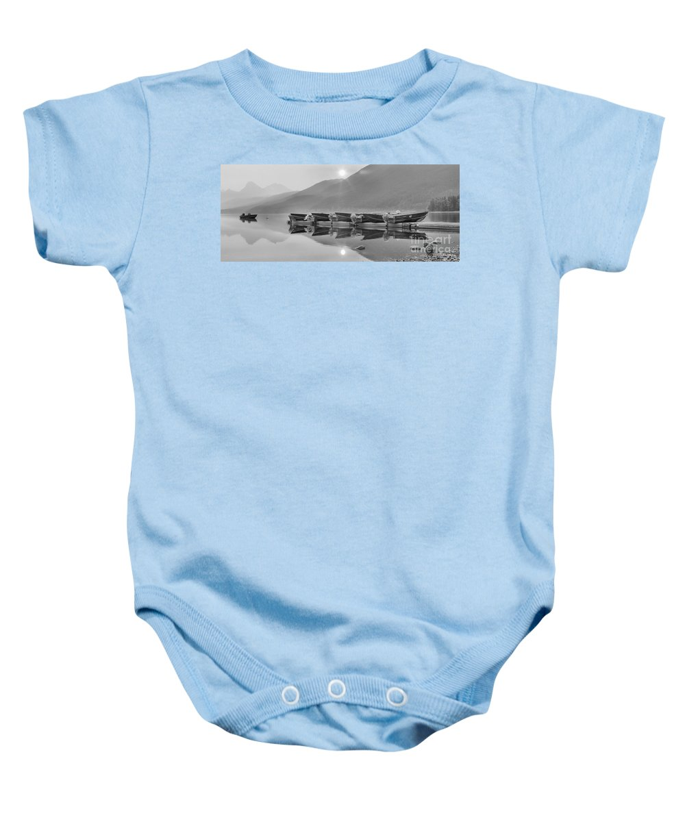 Lake Mcdonald Baby Onesie featuring the photograph Sun Through The Smoke At Mcdonald Black And White by Adam Jewell