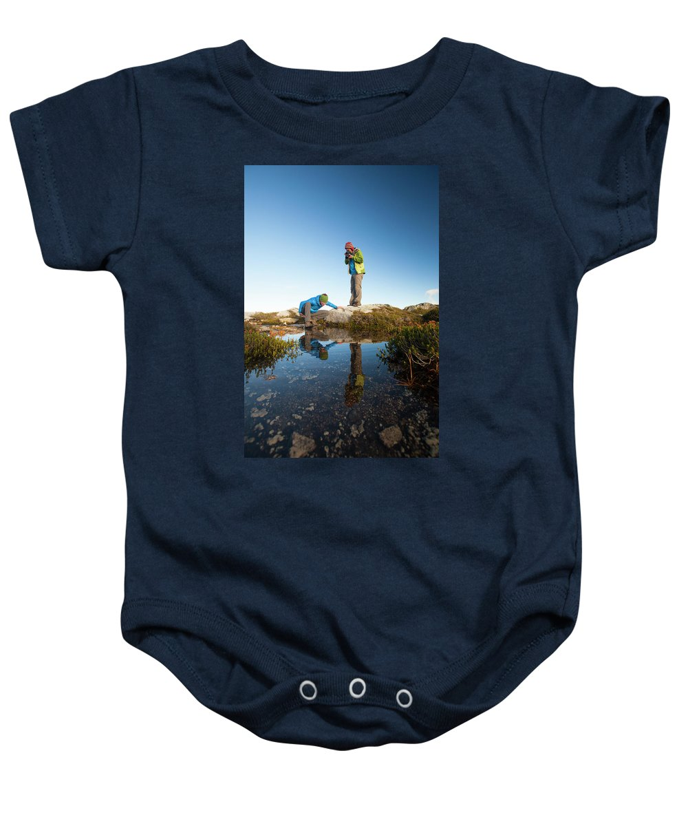 Alpine Baby Onesie featuring the photograph A Young Woman Explores The Microclimate by Christopher Kimmel
