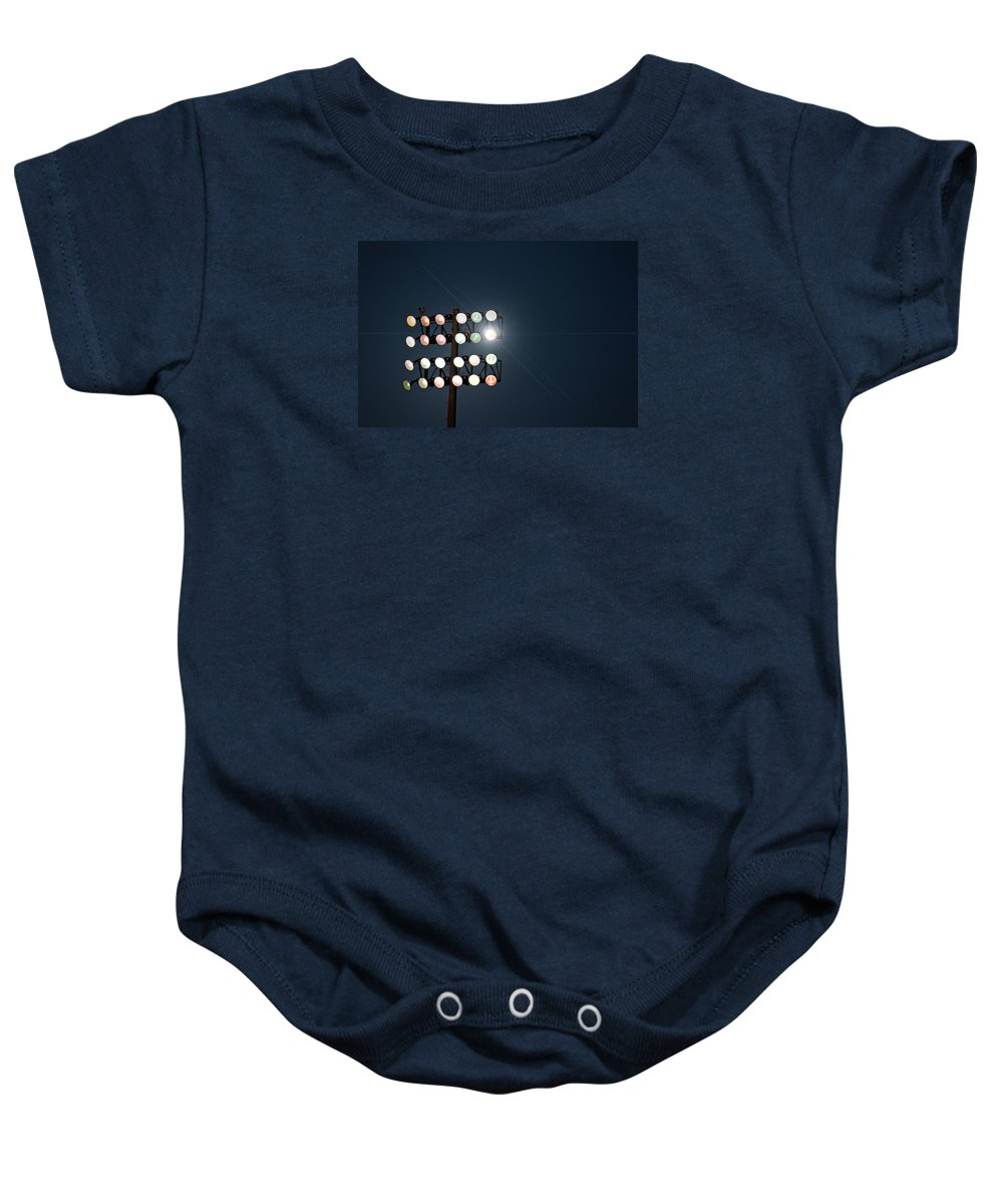 Lights Baby Onesie featuring the photograph Beneath Friday Night Lights by Trish Mistric