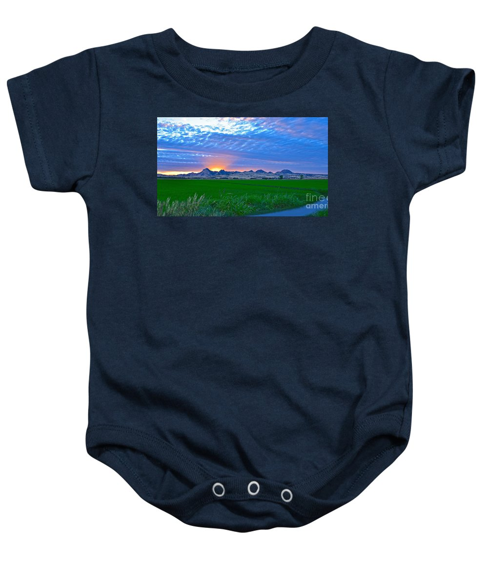 Sutter County Baby Onesie featuring the photograph Sutter Buttes Sunset Ray Burst In The Rice Fields by Michelle Zearfoss