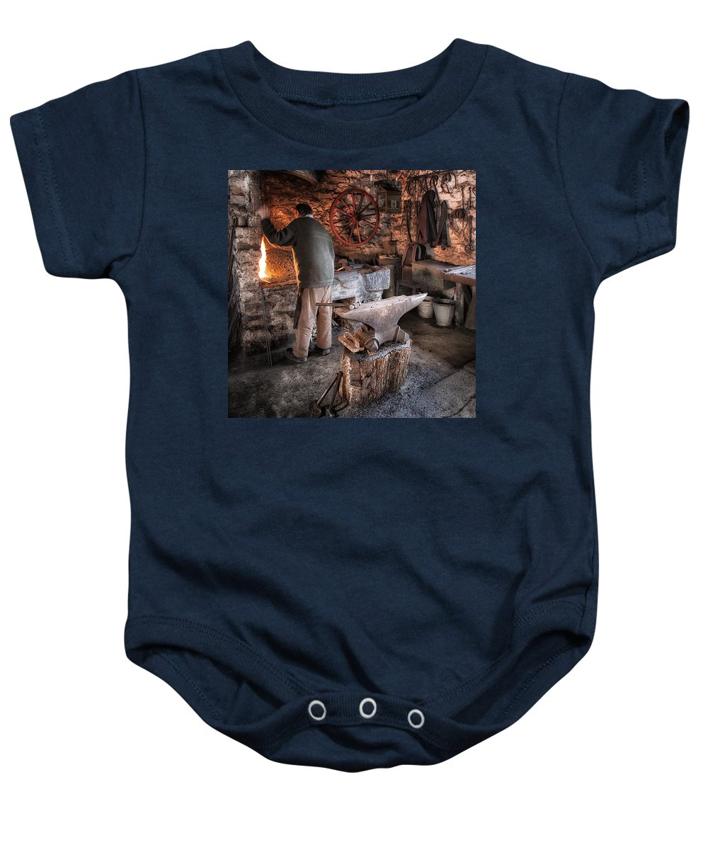 Blacksmith Baby Onesie featuring the photograph The Blacksmith by Nigel R Bell