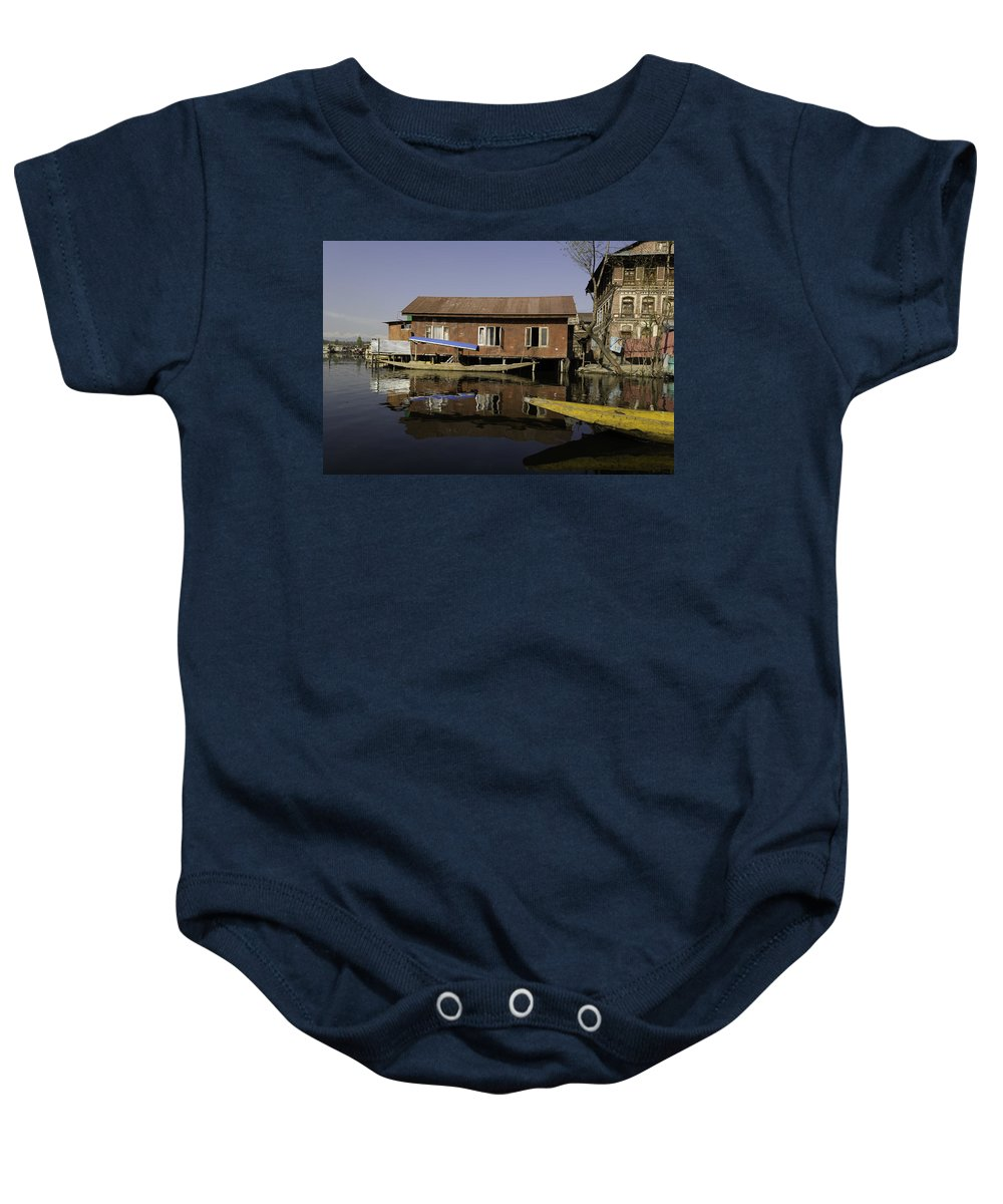 Action Baby Onesie featuring the photograph Yellow Shikara In Front Of A Run Down Area Of Houses In The Dal Lake by Ashish Agarwal