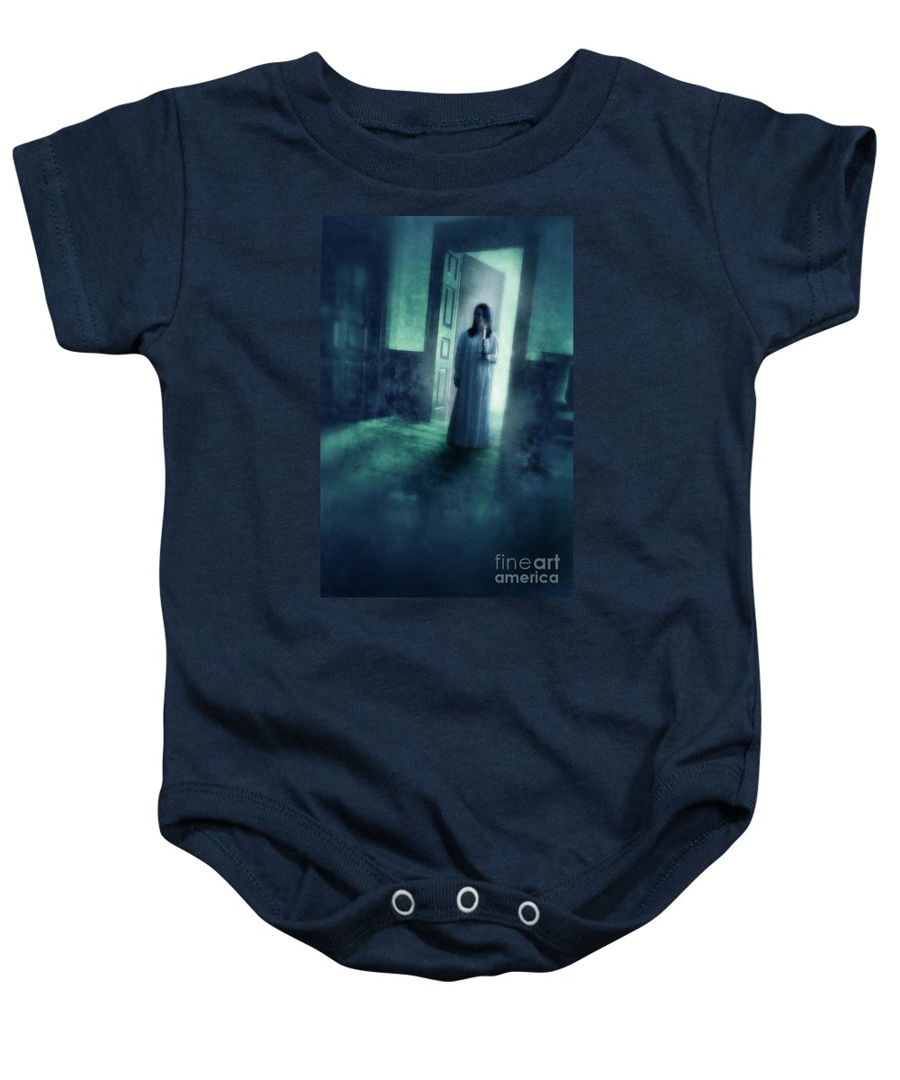 Woman Baby Onesie featuring the photograph Girl With Candle In Doorway by Jill Battaglia