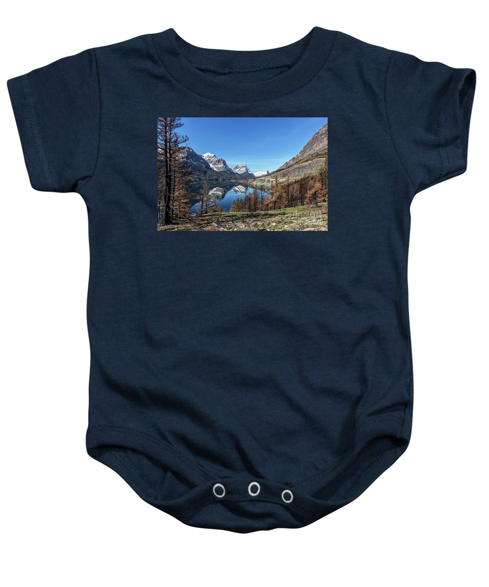 Lake Baby Onesie featuring the photograph Reflection On St Mary Lake Through Burned Trees by Heavens Peak