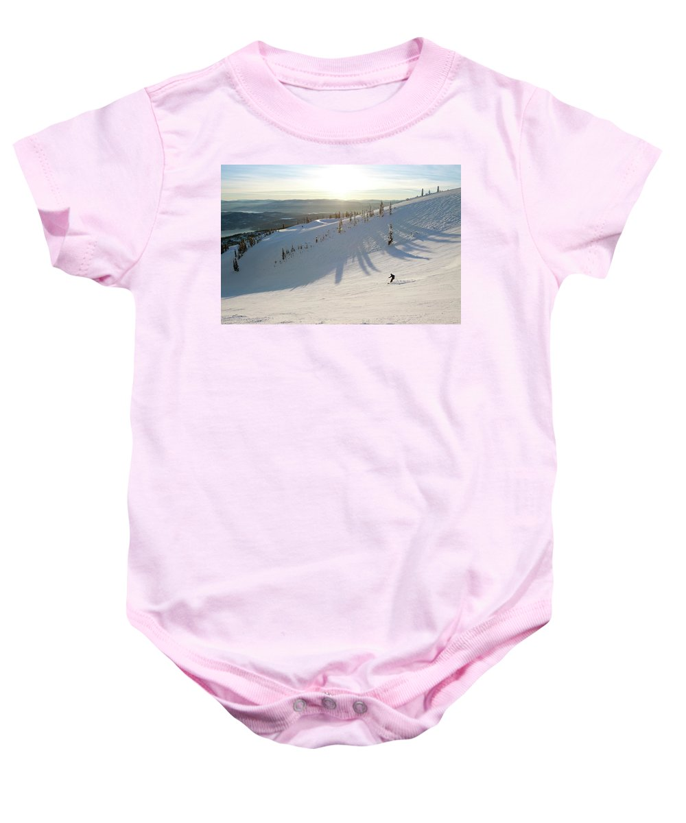 Extreme Sports Baby Onesie featuring the photograph A Lone Skier Makes A Turn At Whitefish by Craig Moore