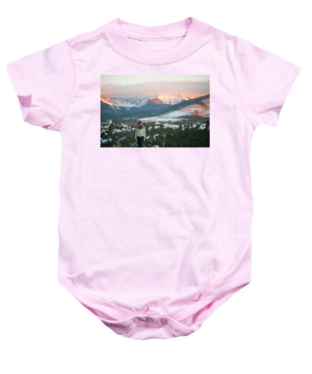 30-34 Years Baby Onesie featuring the photograph A Woman Stands Against A Snowy Mountain by David Zentz