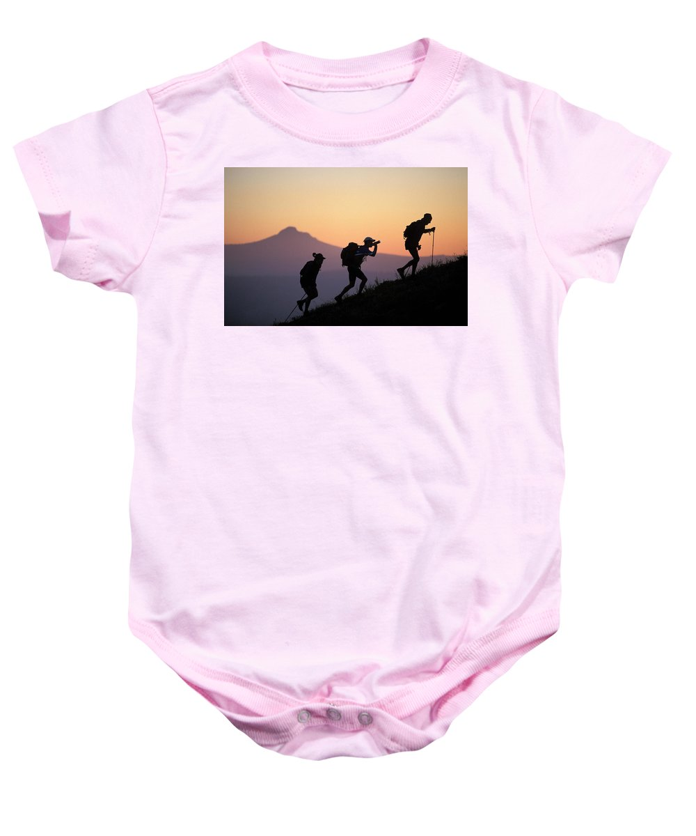 Action Baby Onesie featuring the photograph Adventure Racing Team Hiking At Sunset by Corey Rich