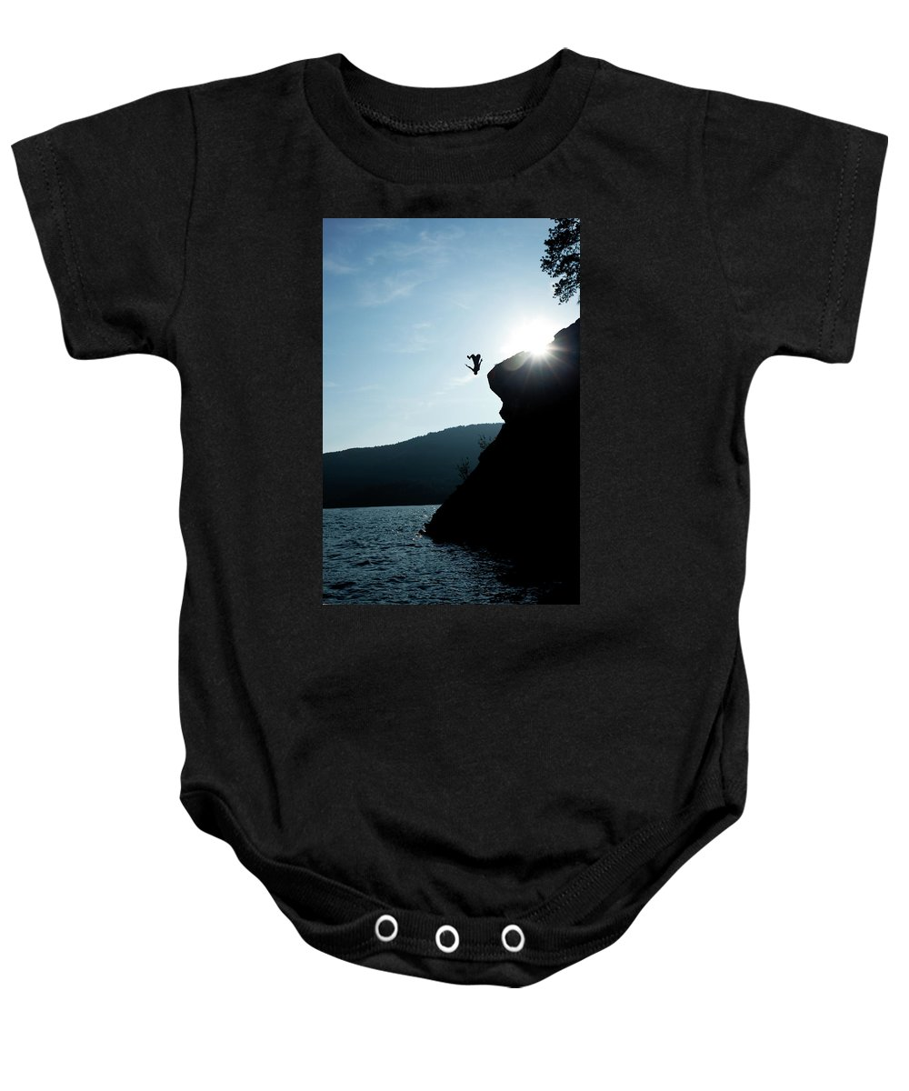Back Lit Baby Onesie featuring the photograph A Young Man Flips Off A Rock by Patrick Orton
