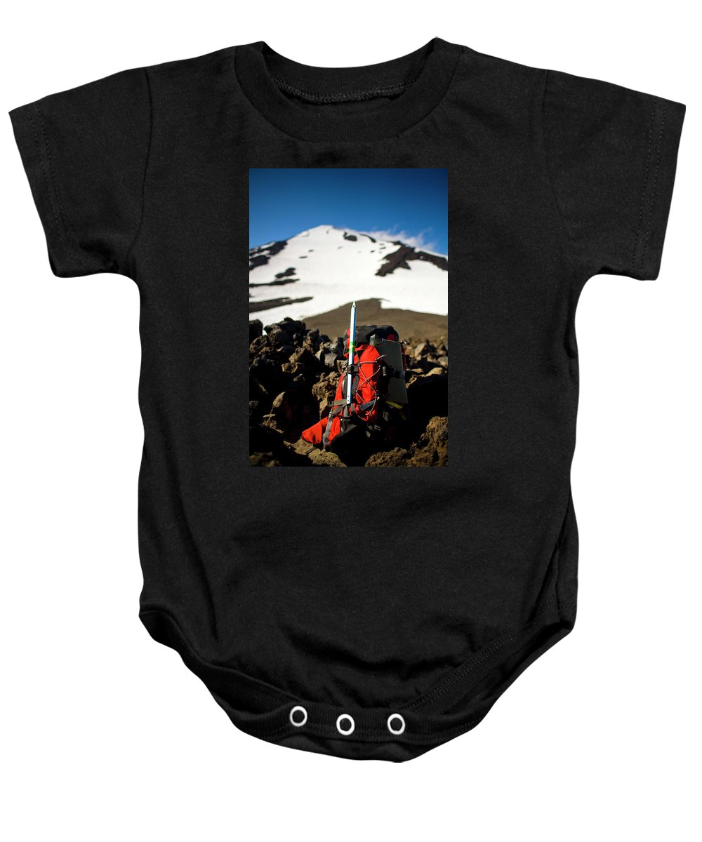 Alpine Baby Onesie featuring the photograph A Backpack Sits On Rocks by Kirk Mastin