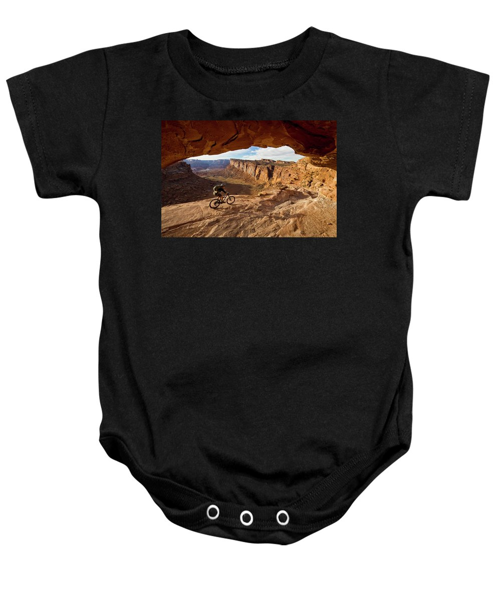 Activity Baby Onesie featuring the photograph A Mountain Biker Rides By On Slickrock by Whit Richardson