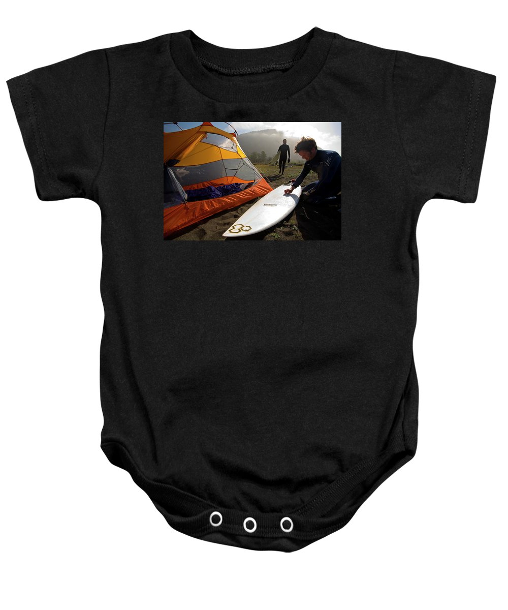 Athlete Baby Onesie featuring the photograph A Pair Of Surfers Prepare To Surf by Corey Rich