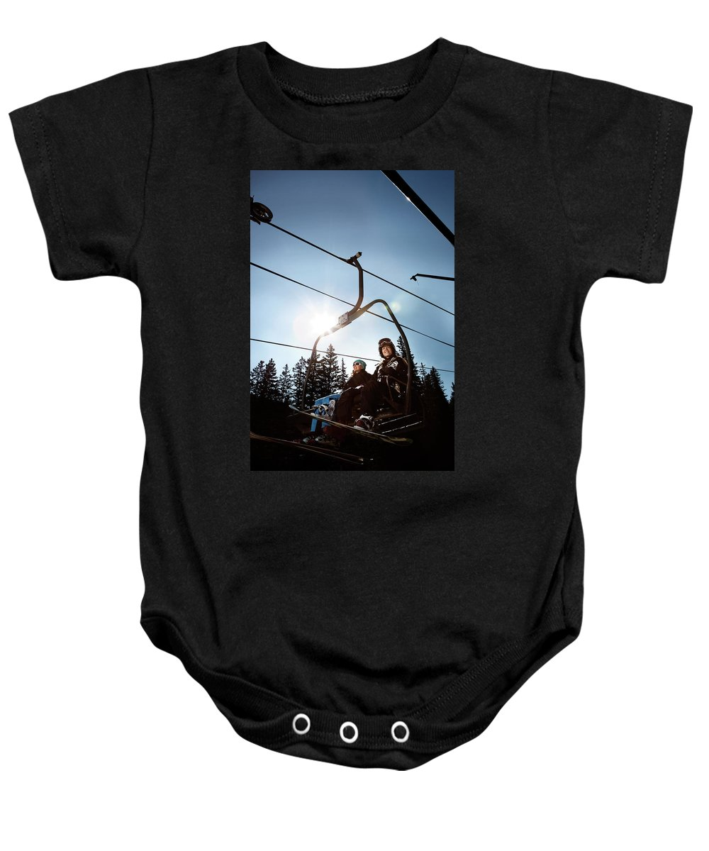 20s Baby Onesie featuring the photograph A Skier And Snowboarder Share The Chair by Ryan Heffernan