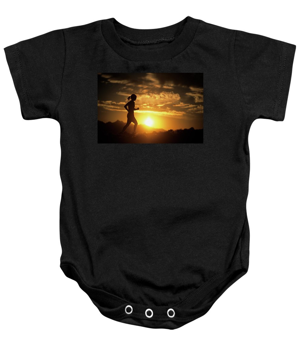 Color Image Baby Onesie featuring the photograph A Woman Jogs Under Sunset by Christian Pondella