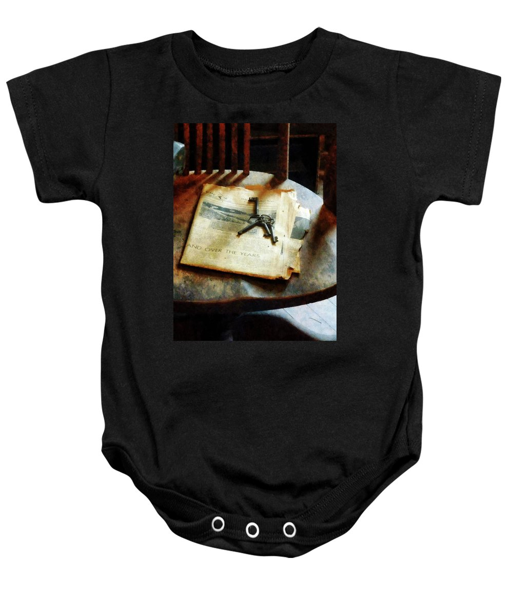 Keys Baby Onesie featuring the photograph Antique Keys On Newspaper by Susan Savad