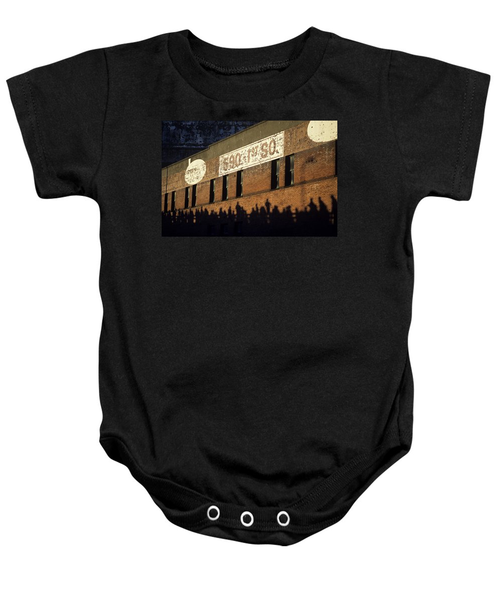 Training Baby Onesie featuring the photograph Downtown Seattle With Silhouetted Runners On Brick Wall Early Mo by Jim Corwin