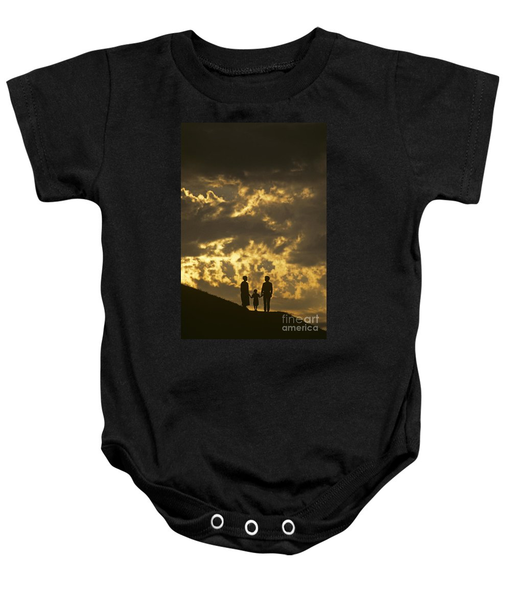 Silhouetted Baby Onesie featuring the photograph Family On Hillside Holding Hands And Facing Life Together. by Jim Corwin