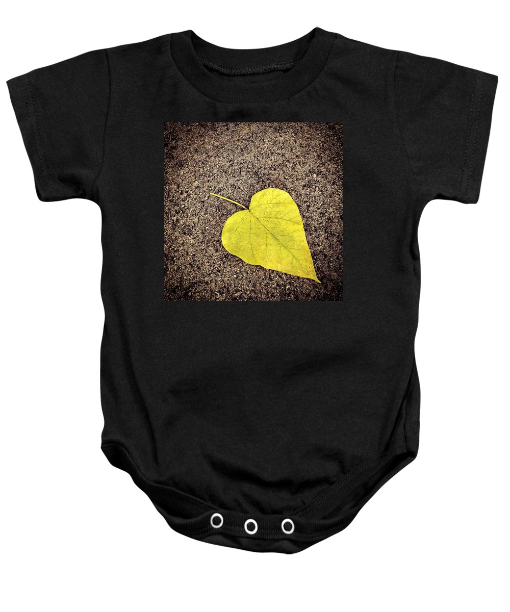 Leaf Baby Onesie featuring the photograph Heart Shaped Leaf On Pavement by Angela Rath