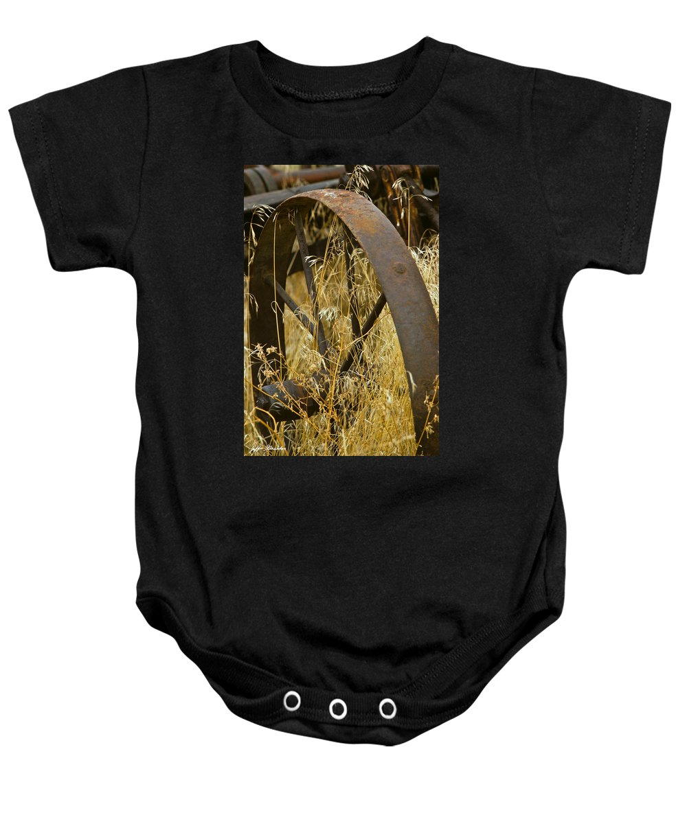 Agricultural Activity Baby Onesie featuring the photograph Rusty Old Wheel And Yellow Grasses by Jeff Goulden