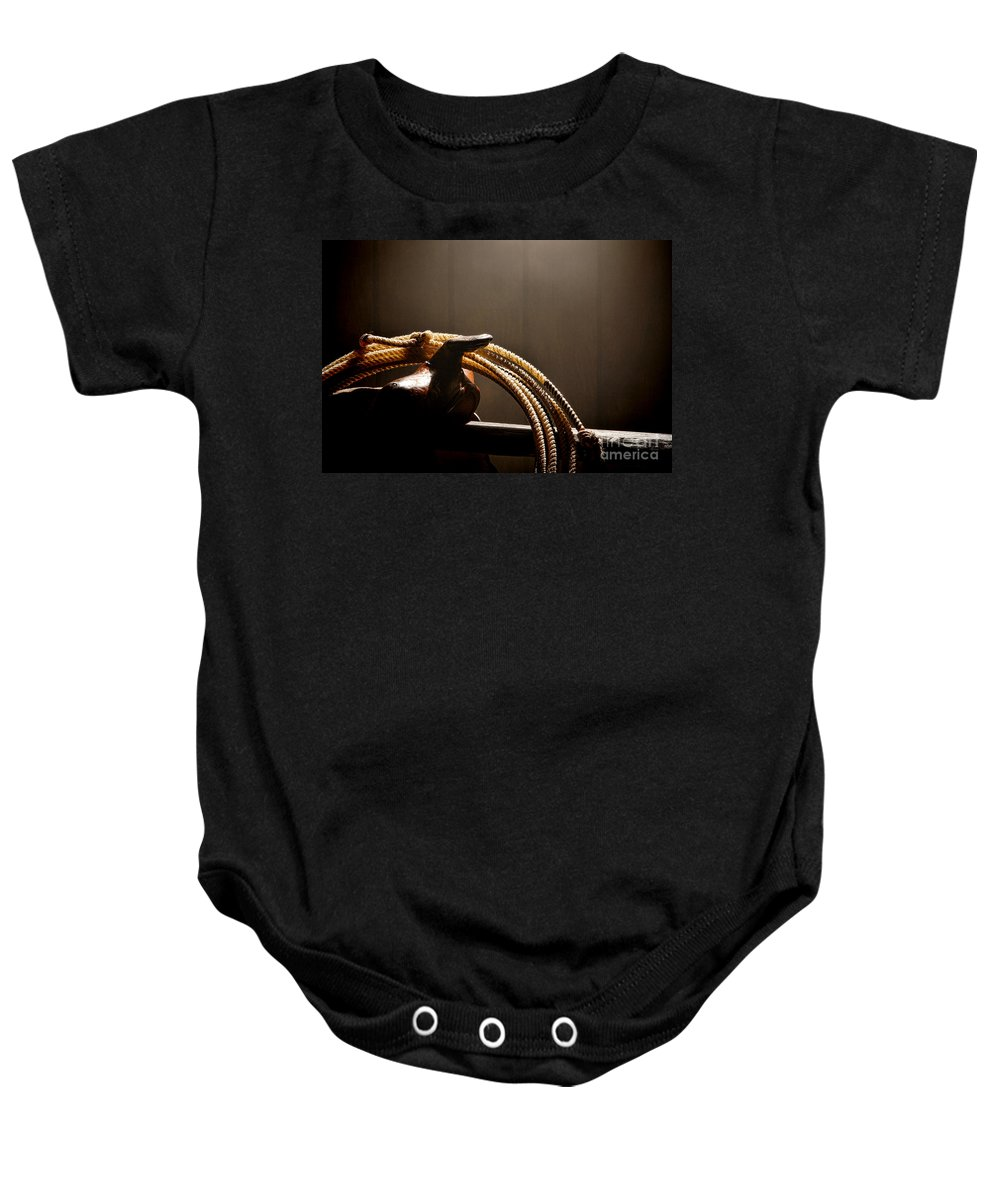 Cowboy Baby Onesie featuring the photograph Saddle In A Barn by Olivier Le Queinec