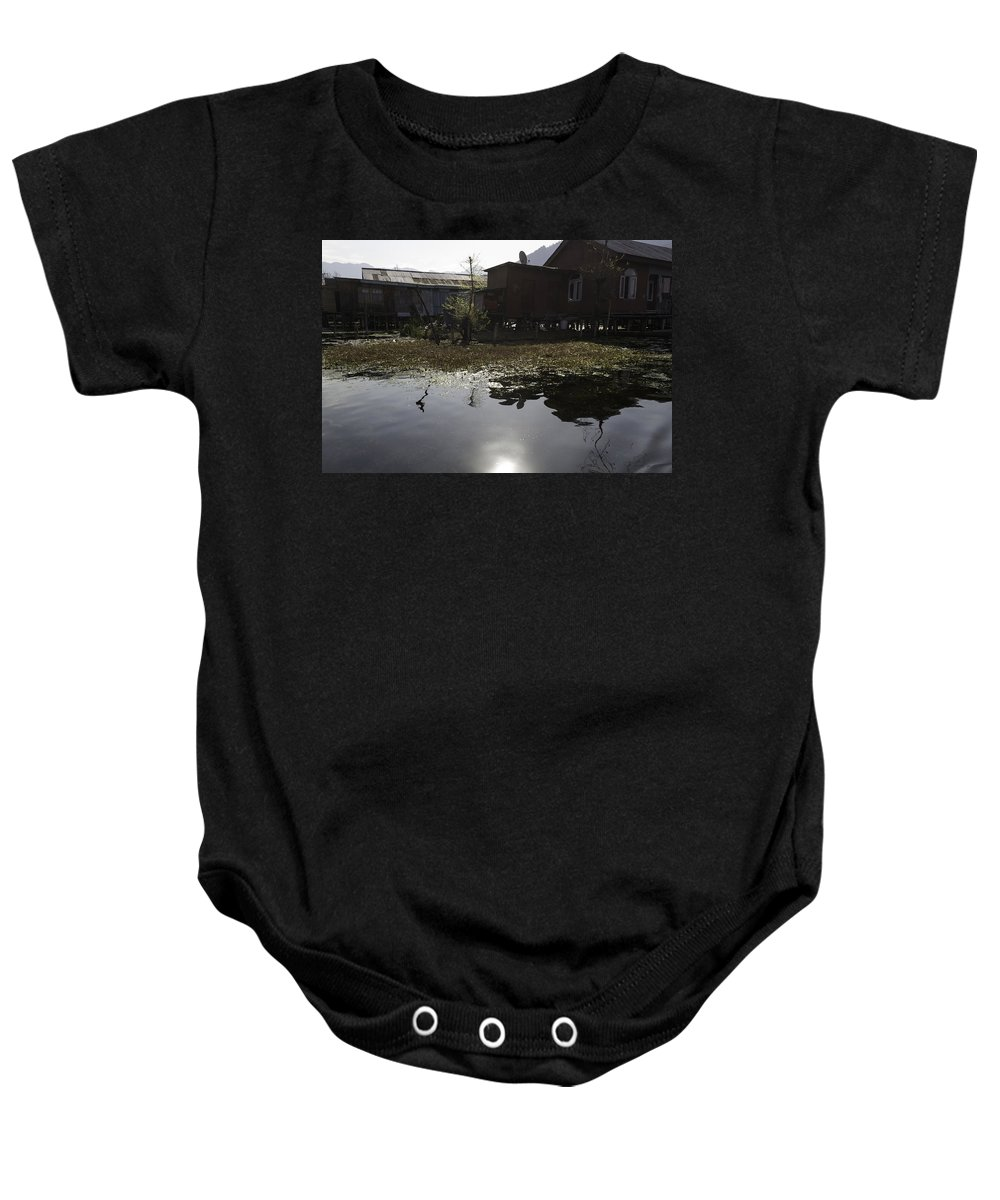 Action Baby Onesie featuring the photograph Shack And House Along With Weeds Right On Shore Of Dal Lake by Ashish Agarwal