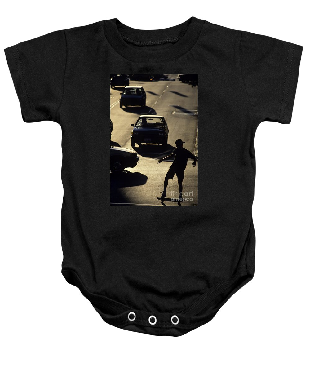 Silhouetted Baby Onesie featuring the photograph Silhouetted Skateboarder by Jim Corwin