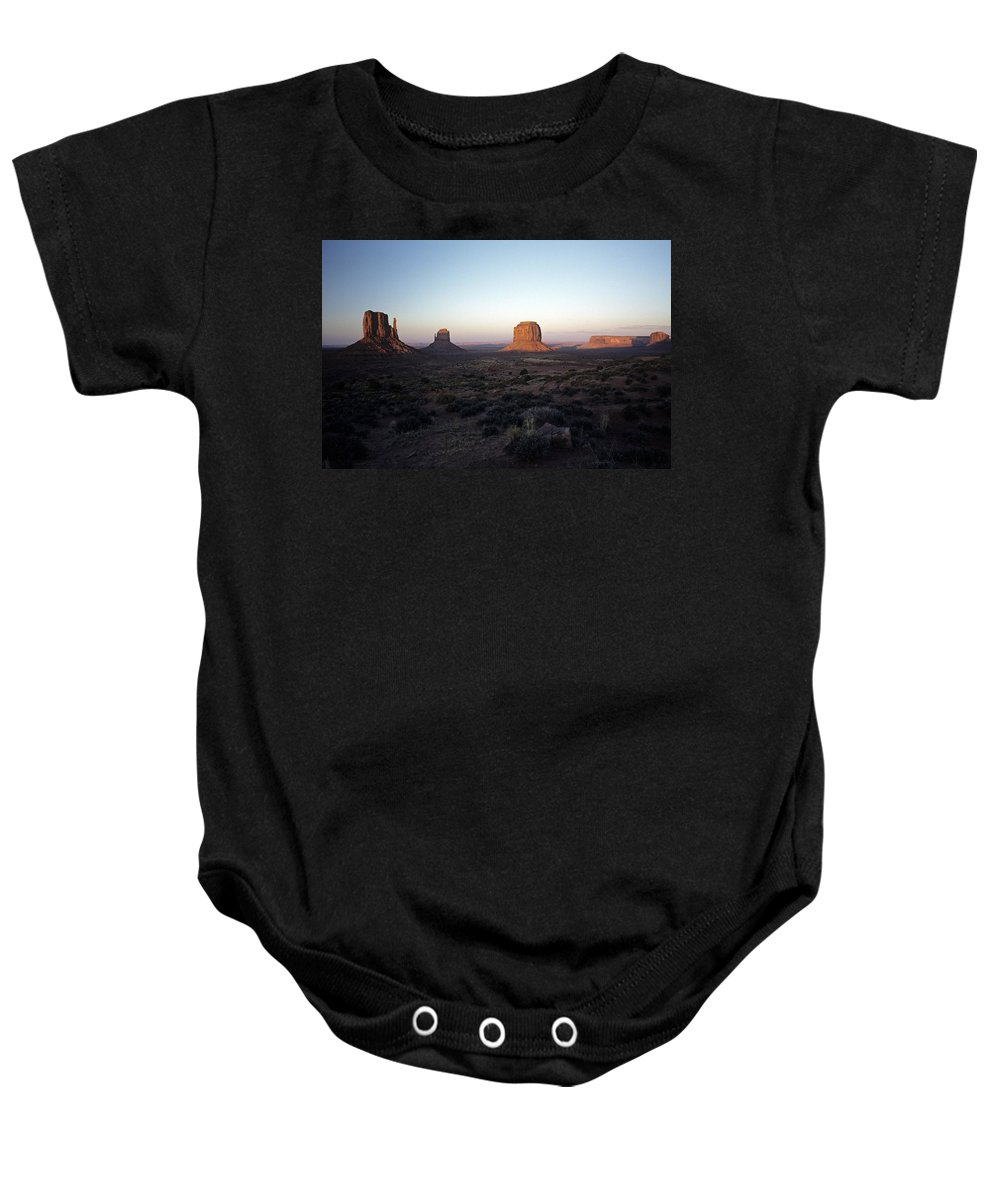 Arizona Baby Onesie featuring the photograph Sunset Light With Mittens And Desert In Monument Valley Arizona by Jim Corwin