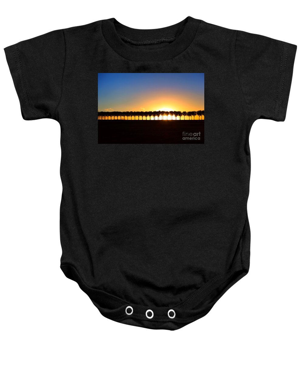 France Baby Onesie featuring the photograph Sunset Over Tree Lined Road by Olivier Le Queinec