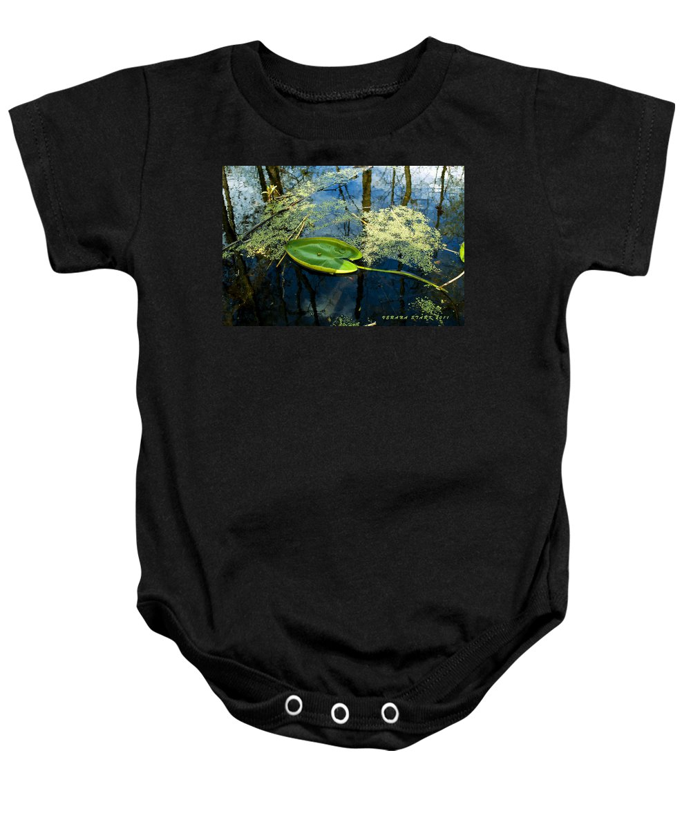 Leaf Baby Onesie featuring the photograph The Floating Leaf Of A Water Lily by Verana Stark
