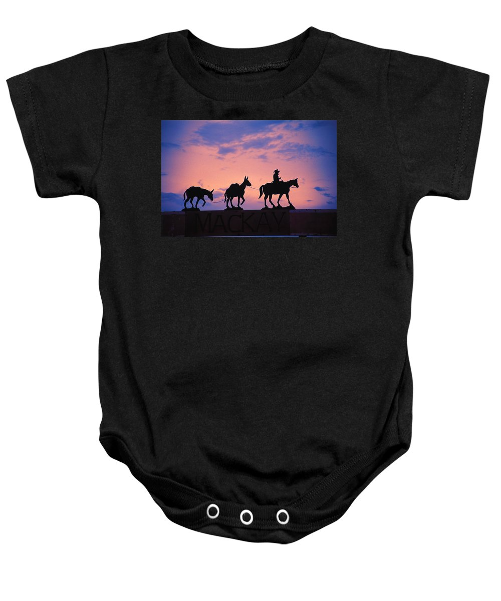 Journey Baby Onesie featuring the photograph Silhouette Of Donkey Train Statue by Corey Hochachka
