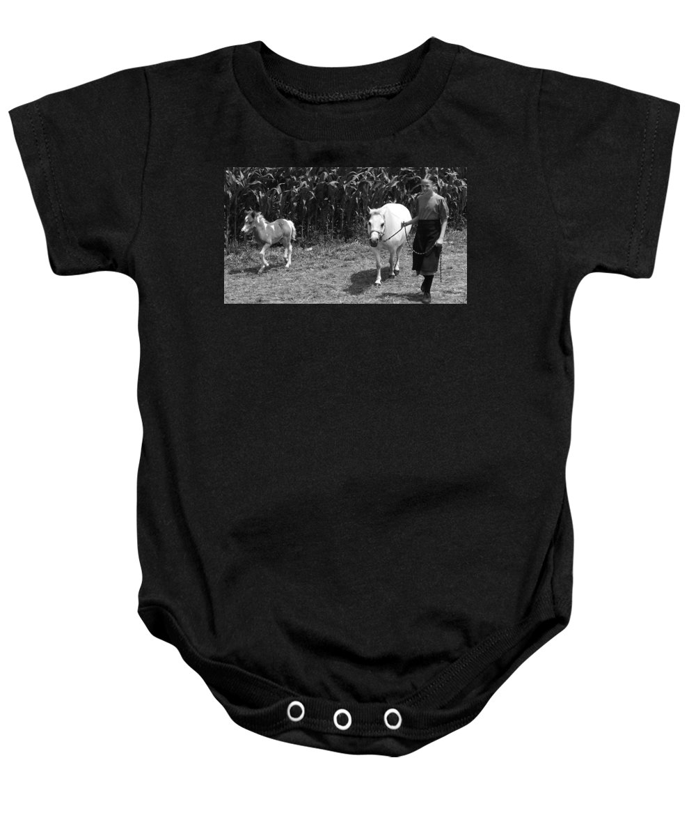 Amish Girl With Her Colt Baby Onesie featuring the photograph Amish Girl With Her Colt by Eric Schiabor