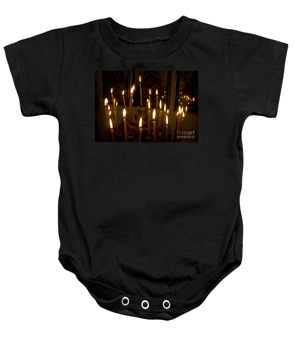 Lit Baby Onesie featuring the photograph lit Candles in church by Danny Yanai
