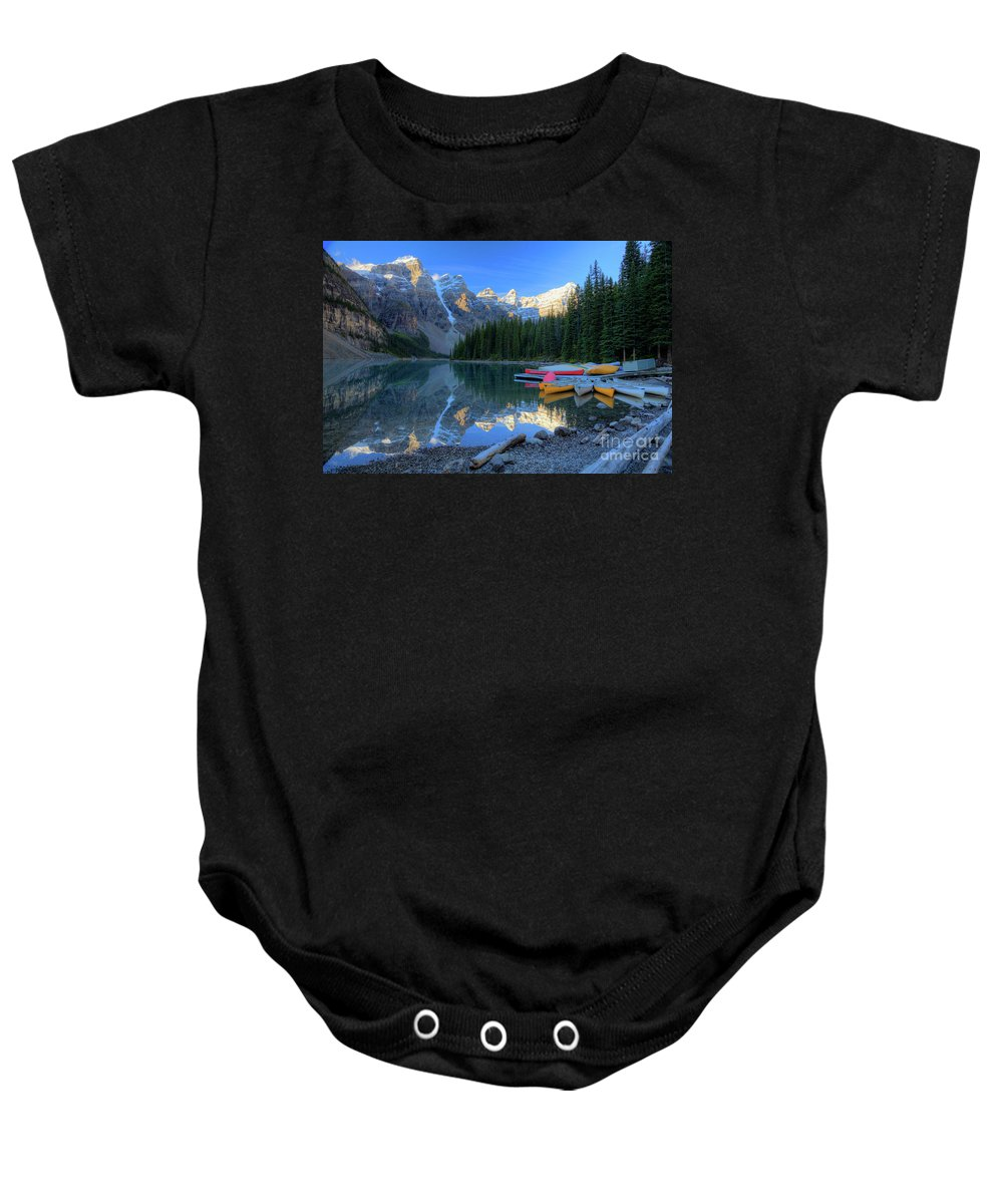 Autumn Baby Onesie featuring the photograph Moraine Lake Sunrise Blue Skies Canoes by Wayne Moran