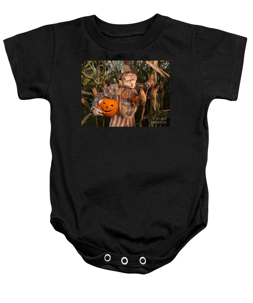 Scarecrow Baby Onesie featuring the photograph Scarecrow With A Carved Pumpkin In A Corn Field by Oleksiy Maksymenko