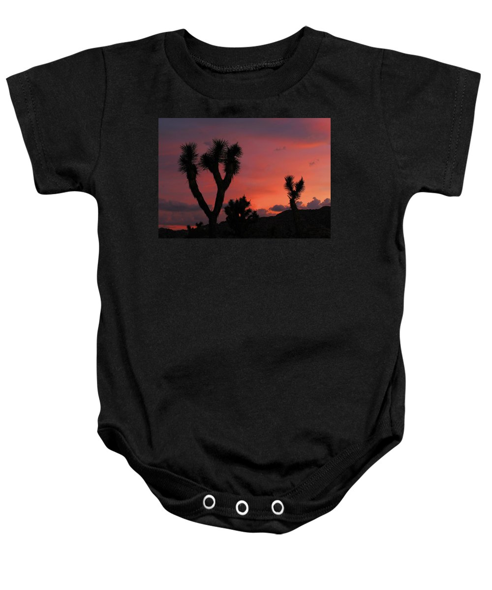 Joshua Baby Onesie featuring the photograph Joshua Trees Silhouetted Against A Red Sky by Angel La Canfora