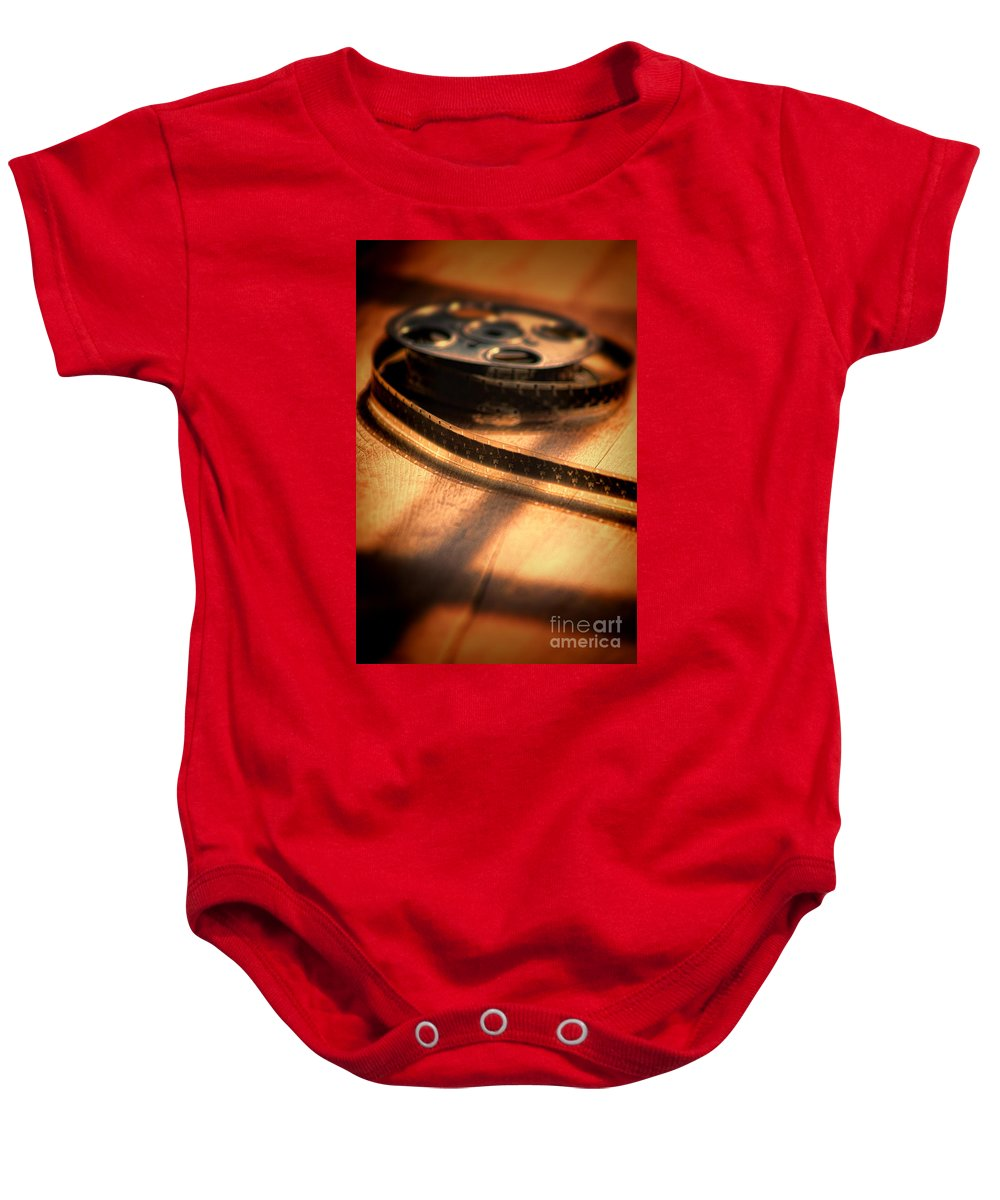 Film Baby Onesie featuring the photograph Film Reel by Jill Battaglia