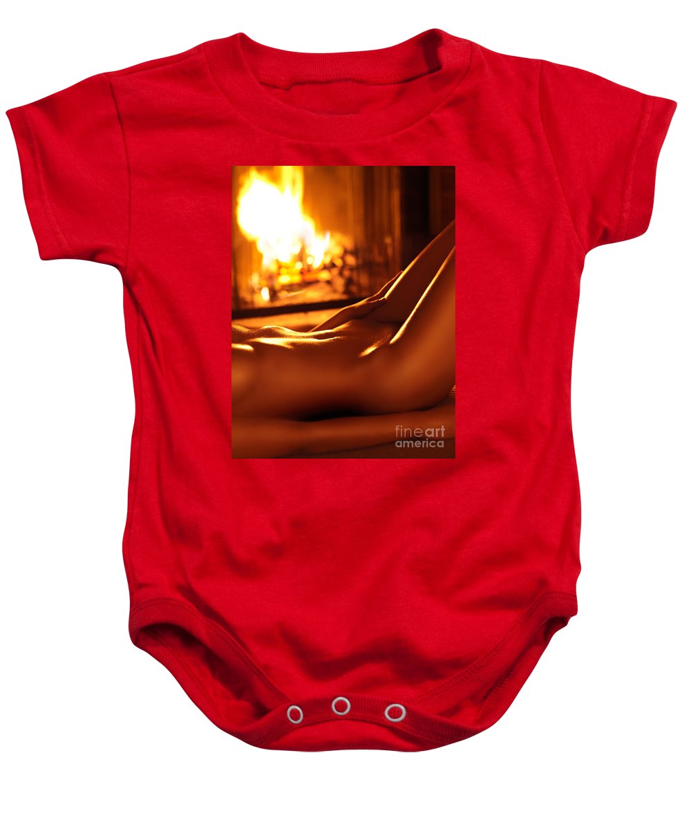 Nude Baby Onesie featuring the photograph Nude Shiny Woman Body In Front Of Fireplace by Oleksiy Maksymenko