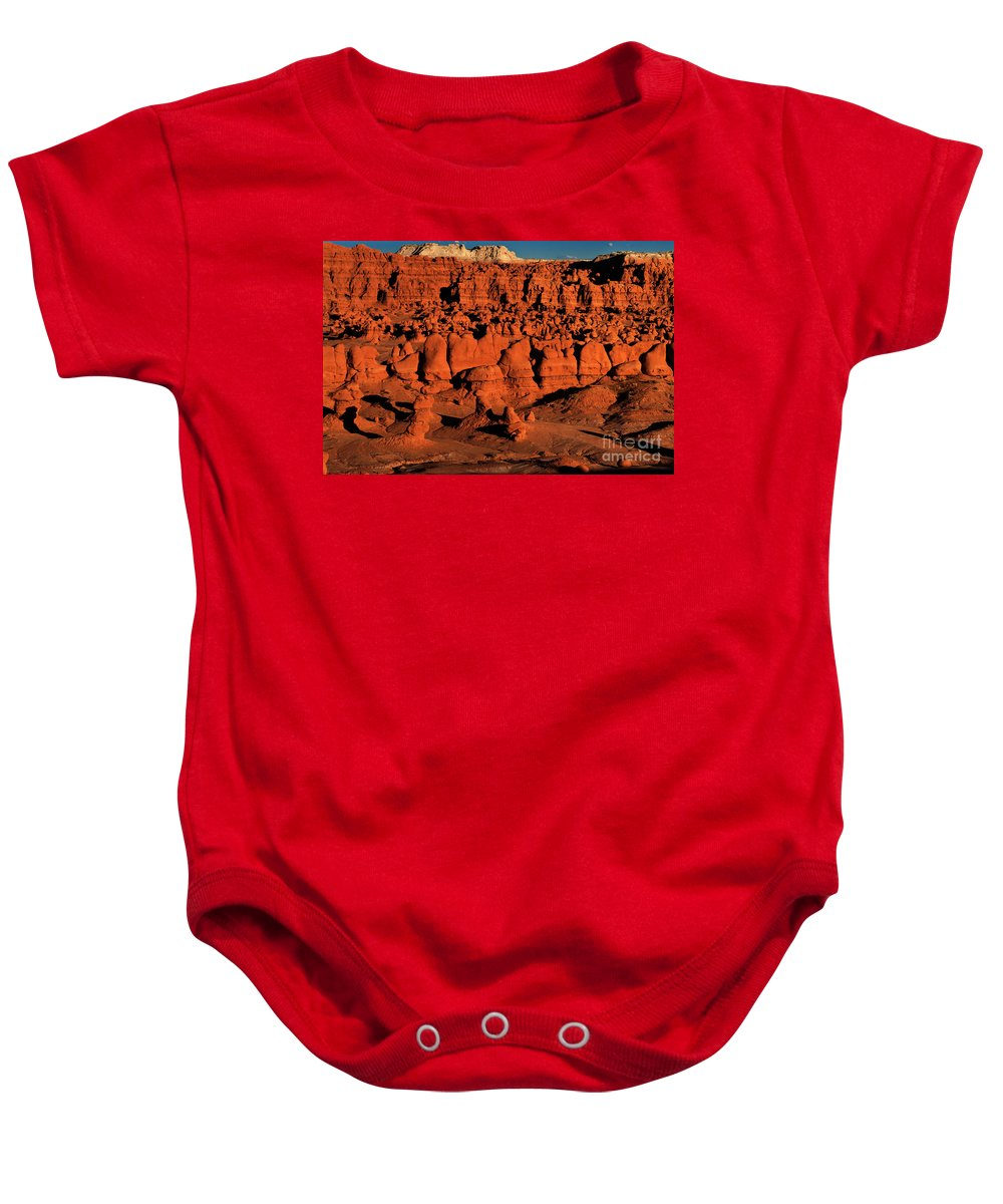 North America Baby Onesie featuring the photograph Sunset Light Turns The Hoodoos Blood Red In Goblin Valley State Park Utah by Dave Welling