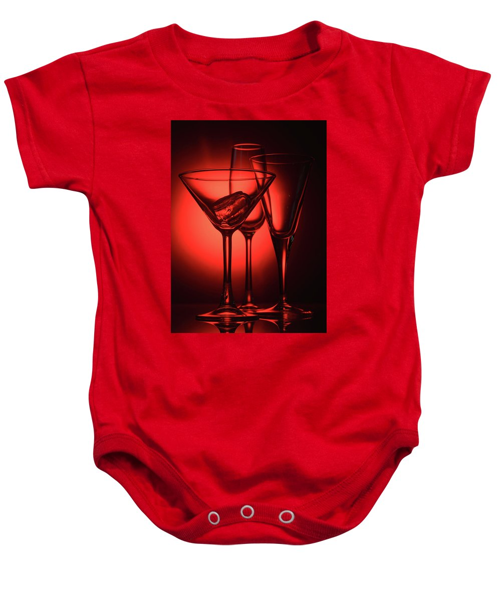 Alcohol Baby Onesie featuring the photograph Three Empty Cocktail Glasses On Red Background by Oleg Yermolov