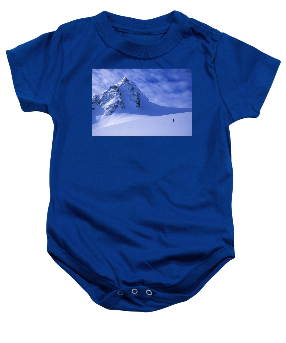 Adventure Baby Onesie featuring the photograph A Woman Ski Tours And Explores by Jimmy Chin